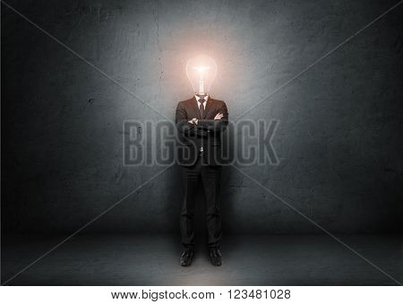 Businessman with light bulb instead of head on a concrete room. Concept of idea.
