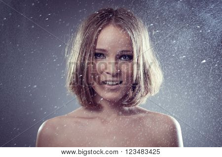 happy attractive woman smiles in rain and catches drops for your design