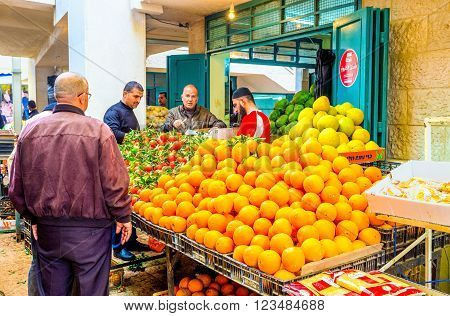BETHLEHEM PALESTINE - FEBRUARY 18 2016: The merchant sells fruits to clients in Bethlehem market on February 18 in Bethlehem.