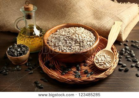 Sunflower oil and seeds on wooden table background, closeup