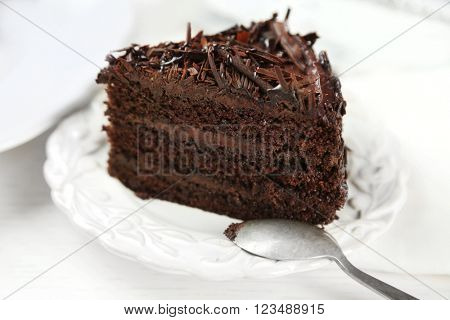 Sliced chocolate cake on wooden table, on light background