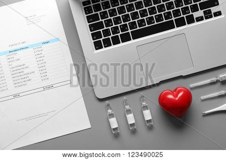 Doctor table with medicines, red heart and laptop, top view