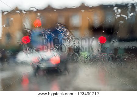 Blurred picture of traffic through a car windscreen during heavy rain.