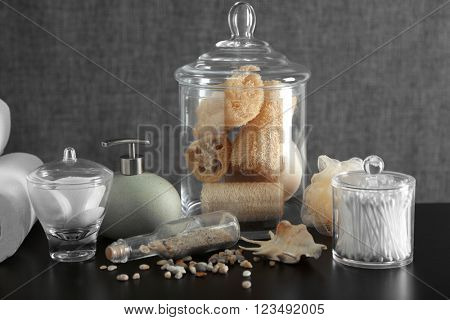 Bathroom set with dispenser, wisps and sponges on grey background