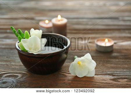 Beautiful flower in the bowl with water and candles on wooden background