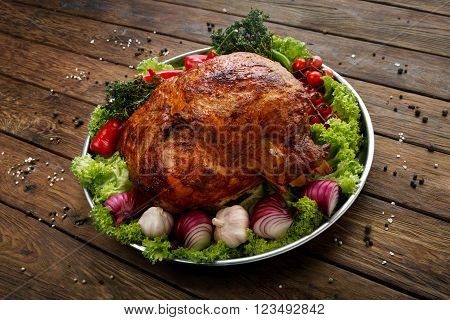 Restaurant food, roasted pork shoulder. Meat dish. Festive banquet dish, holiday dish. Catering. Served main dish, roasted pork with vegetables and herbs. Plate at wooden rustic background.