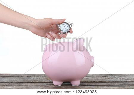 Piggy bank and a hand holding pocket watch above it on white background