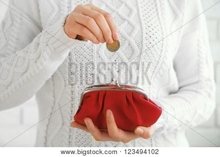 Woman takes out money from a red wallet