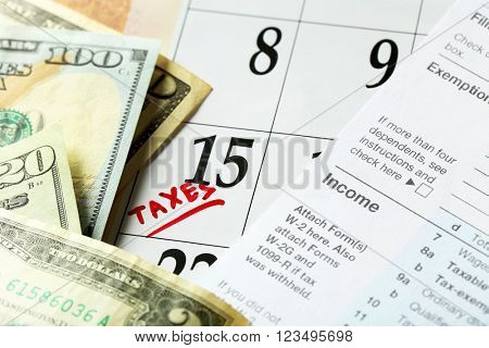 A red tax mark in the calendar, tax form with dollar bills, close up