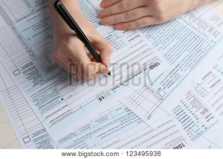 Female hand holding a black pen and filling in the 1040 Individual Income Tax Return Form for 2015 year on the white desk, close up