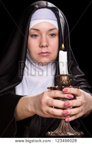 Nun holds a burning candle in his outstretched hands. Candle clearly nun blurry. Isolated on black background