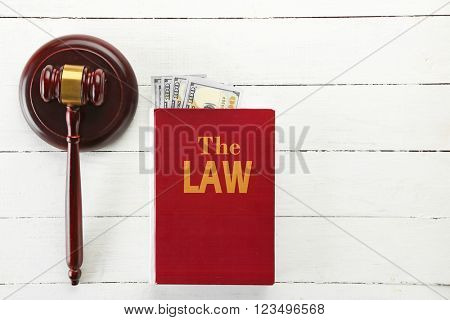 Gavel with book and money on wooden table, top view