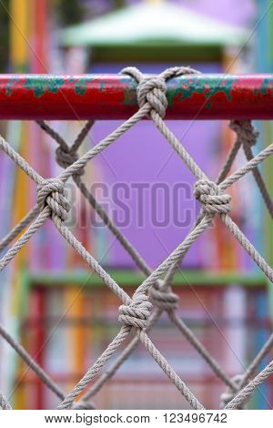Climbing Net in playground for children climb up on blur colorfull background