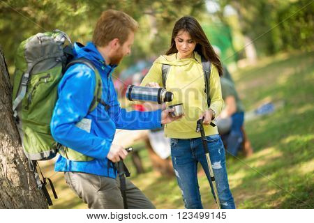 Young female hikers pours water from thermos to his male friend in nature