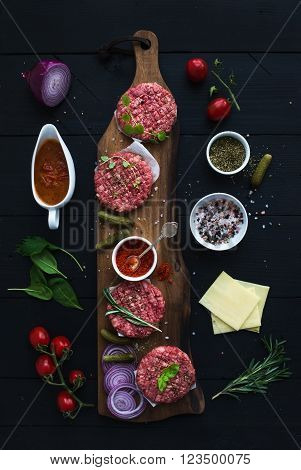 Ingredients for cooking burgers. Raw ground beef meat cutlets on wooden chopping board, red onion, cherry tomatoes, greens, pickles, tomato sauce, cheese, herbs and spices over black background, top view