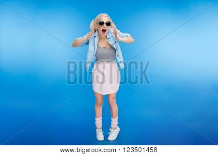 Full length portrait of a cheerful attractive woman looking at camera over blue background
