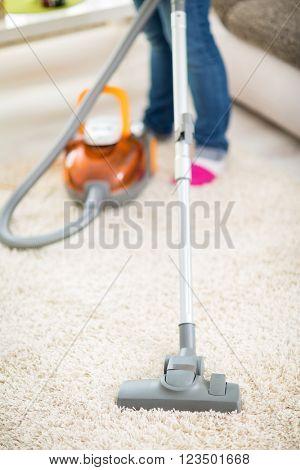 Close up of vacuuming carpet in apartment with vacuum cleaner