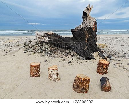 Log stools in front of the remains of a burnt piece of driftwood shaped like a spirit crying into the sky.