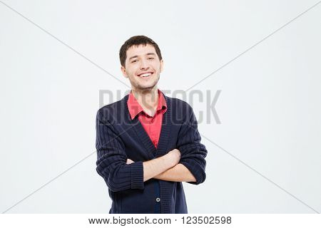 Smiling casual man standing with arms folded isolated on a white background