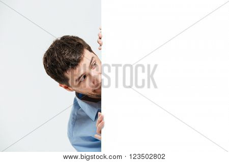 Businessman peeking from blank board isolated on a white background