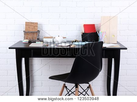 Workplace with table, stationery and chair in room interior
