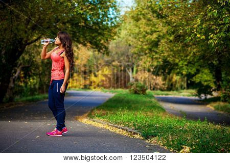 a girl drinks water after sport
