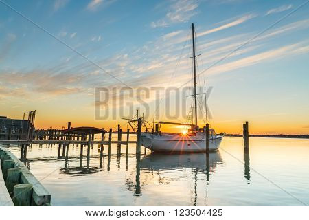 The sun sets as a sailboat rests at the dock waiting for warmer days and its next excursion.