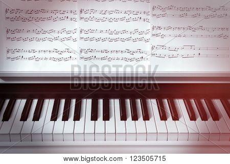 Piano keyboard and musical notes close up