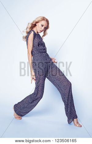 Beautiful blond woman in summer satin stylish overalls