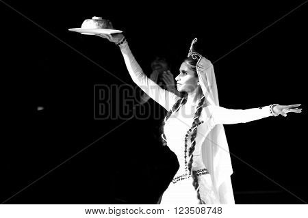 BAKU, AZERBAIJAN - JANUARY 18 2014  Traditional Azerbaijani wedding dance: woman with rice. A dancer in a white dress carries a symbolic dish of rice to the newly married couple at a wedding reception in Azerbaijan