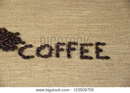 The word coffee created by coffee beans on brown burlap.