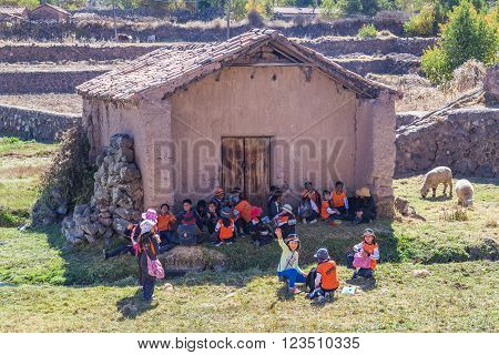 Ollantaytambo, Peru - Circa June 2015: Children In Traditional Peruvian Clothes Are Waiting For A Sc