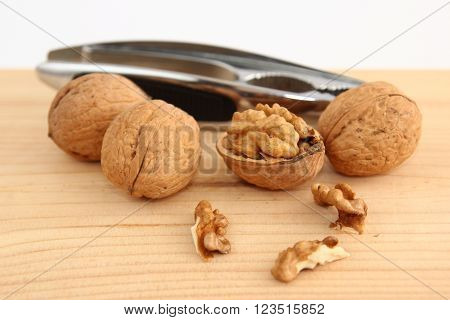 English or Persian walnuts and metal nutcracker on a wooden background