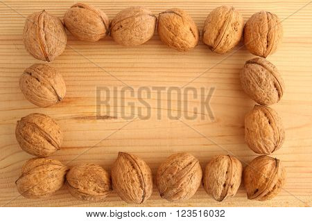 English or Persian walnuts on a wooden background.