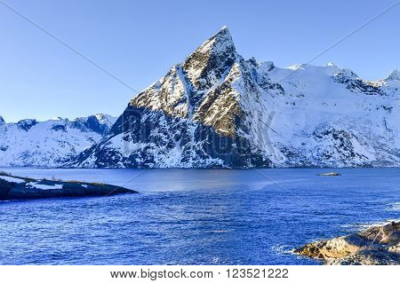 Fishing hut (rorbu) in the Hamnoy and Lilandstinden mountain peak in winter in Reine Lofoten Islands Norway.