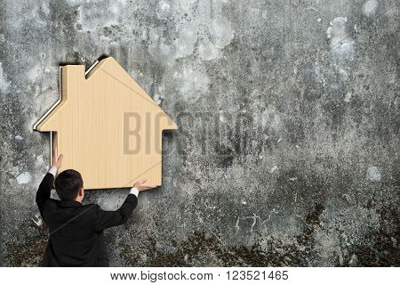 Man putting wooden house into hole of old mottled concrete wall
