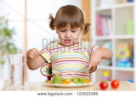 Little child girl refusing to eat her dinner or lunch