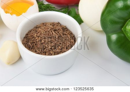 Closeup of cumin seeds in white bowl with foodstuffs on a white background. Food background