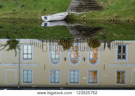 Manor house reflection on water of pond and empty boat ** Note: Visible grain at 100%, best at smaller sizes
