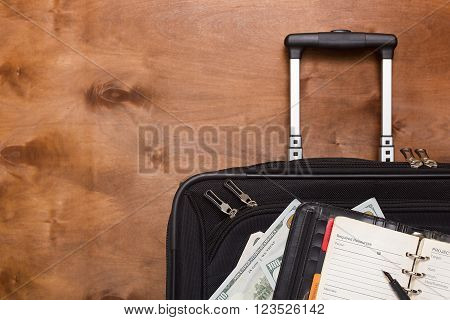 Black suitcase and luggage for a business trip on a wooden background