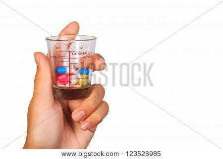 A Human Hand Holding Many Colorful Pills In A Measuring Cup Of Glass On White Background.