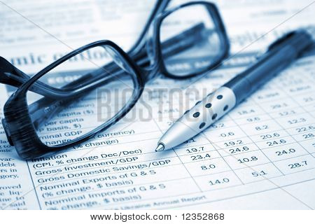 pen and glasses on the financial table