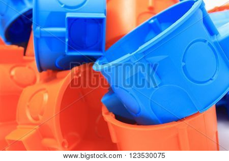 Heap of blue and orange plastic electrical boxes components for electrical installations accessories for engineering jobs