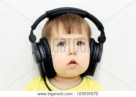 Caucasian little girl attentively listening educational audio program with headphones