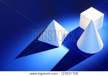Geometry concept. Set of various paper shapes on blue background