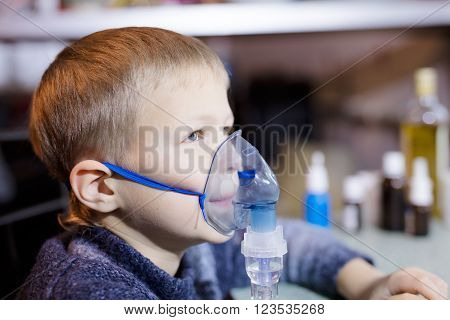 Litle boy sitting with nebulizer mask close up