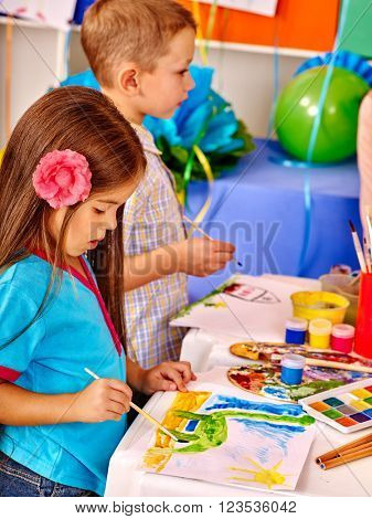 Little girl and boy with brush painting on table in  kindergarten .