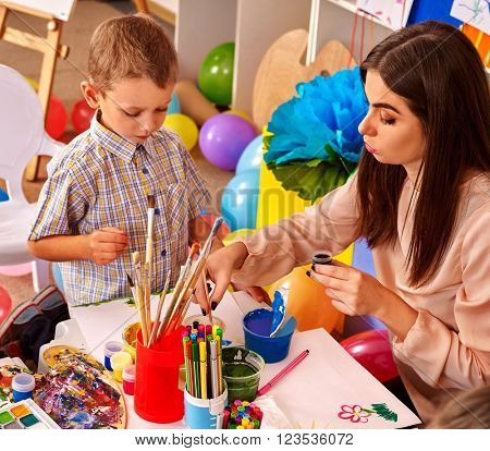 Little boy with teacher woman painting on paper at table  in  school.