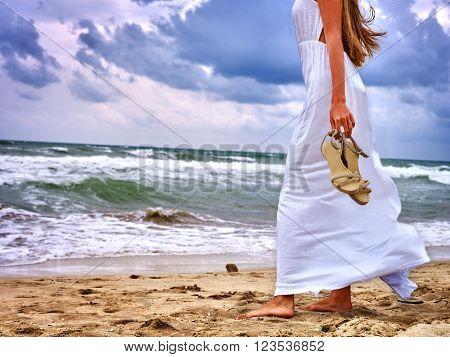 Summer girl sea.  Woman wearing sundress goes on coast.