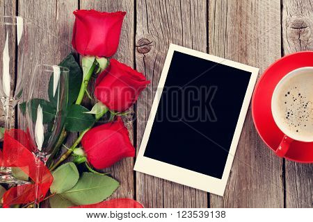 Valentines day greeting card, coffee cup and red roses on wooden table. Top view with copy space. Toned